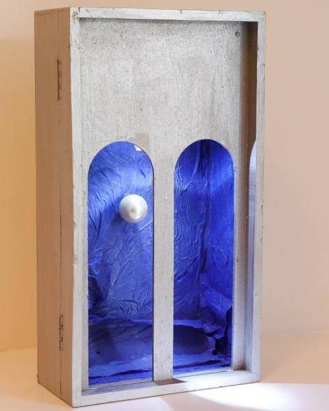 Pearl hung inside a box lined with blue tissue paper